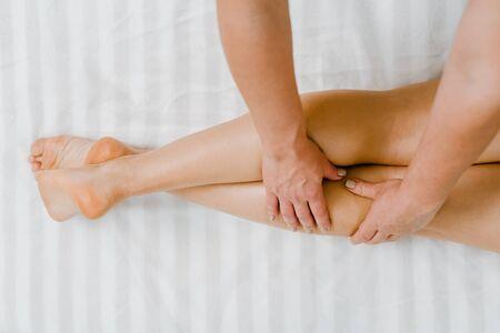Foto de Top view of professional physiotherapist massaging legs of female patien in clinic - Imagen libre de derechos