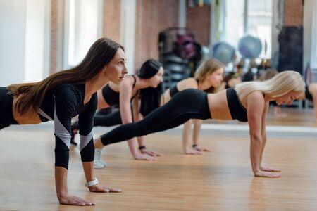 Photo pour Fit young beautiful women doing push-ups in modern gym - image libre de droit