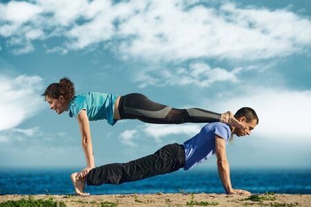 Photo for Healthy man and fit young woman training together and doing acroyoga - Royalty Free Image