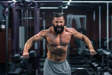 Foto de Muscular athletic bodybuilder working hard in gym on dark background - Imagen libre de derechos
