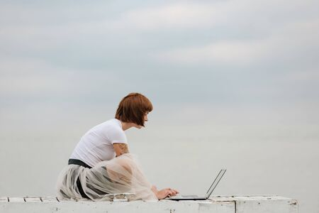 Photo for Young woman checking e-mail on laptop computer while sitting on pier - Royalty Free Image