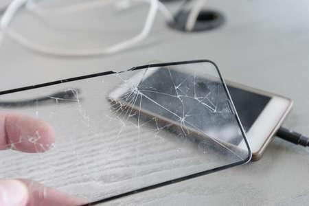 Foto de Broken protective glass on the background of charging mobile phone - Imagen libre de derechos