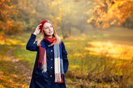 Photo for Blonde happy girl in good mood posing in autumn park, walks for a womans peace of mind - Royalty Free Image