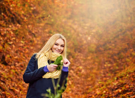 Photo pour Portrait of beautiful happy young girl wearing warm scarf in autumn forest, walks for a womans peace of mind - image libre de droit
