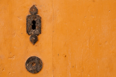 The old iron lock in a yellow wooden door