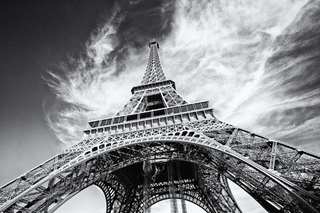 Dramatic view of Eiffel Tower in Paris, France. Black and white image, same film grain added.