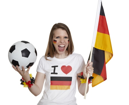 Attractive woman shows german flag and football and screams in front of white background