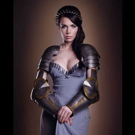 Photo pour portrait of a beautiful lady warrior, dark-haired girl in a gray dress. bright makeup, hairstyle, spikes - image libre de droit