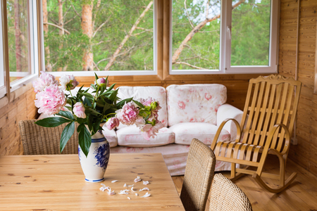 A cozy terrace with furniture - a wooden rocking chair, a sofa, peonies in a vase on the table and wicker chairs with a view of the forest
