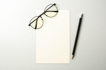 Photo pour blank note paper and a pencil on grey desk background. - image libre de droit