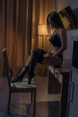 Sexy girl sitting on the table and adjusting stockings