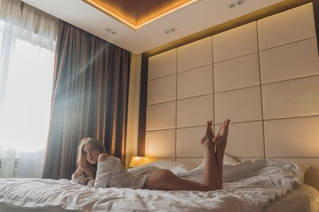Foto de Beautiful blonde with long hair in a mans shirt dangles her legs on the bed in the morning - Imagen libre de derechos