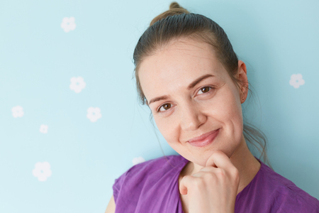 Close up portrait of pretty delighted young woman holds chin, looks positively at camera, enjoys having weekend, dressed in purple clothes, stands against blue wall. People and lifestyle concept