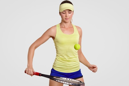 Attractive young female tennis professional player hit tennis ball with racquet, trains in gym, wears headband, shorts and polo shirt, has concentrated expression, isolated over white background.