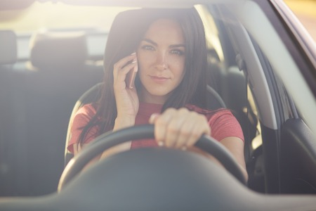Beautiful brunette young female driver speaks via modern cell phone while driving car, has serious exression, discusses something with friend, being stuck in traffic jam, looks through windshiled