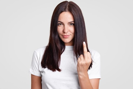 Foto de Bad girl with straight dark hair shows fuck sign, looks mysteriously at camera, wears casual t shirt, isolated over white background. Young brunette young woman shows middle finger. Fuck off! - Imagen libre de derechos