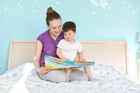 Indoor shot of affectionate woman and small boy read interesting story from book, sit at bed, enjoy calm atmosphere, smile positively. Mother and little male child pose in bedroom. Education
