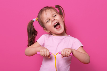 Photo pour Adorable girl holds skipping rope in hands. Charming female child with opened mouth and narrowed eyes with happy expression. - image libre de droit