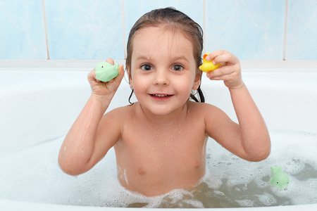 Photo pour Little baby girl holding toy in hands taking bath, plays in water with duck and dolphin. Adorable child being photographed while relaxing with foam in bathroom. Hygiene and health care concept. - image libre de droit