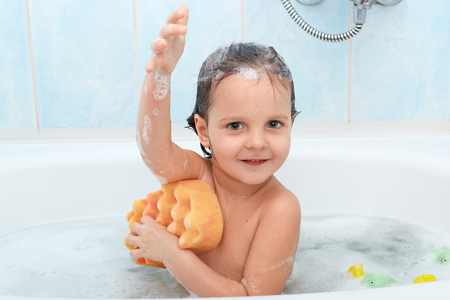 Foto de Cheerful positive adorable small child taking bath and washing herself with yellow sponge, expresses pleasant emotions, being glad to relax, isolated on blue wall in bathroom. Hygiene concept. - Imagen libre de derechos