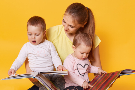 Foto de Young mother and her little babies daughters reading books, look on colourful pages, momny keeps children in her knees while sitting on floor isolated over yellow background. Happy motherhood concept. - Imagen libre de derechos