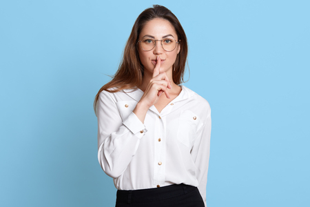 Photo pour European slender woman shows with gesture to keep in silence, holding forefinger near lips, stands firmly and confidently with her long dark hair down and widely open blue eyes. Copy space for ad. - image libre de droit