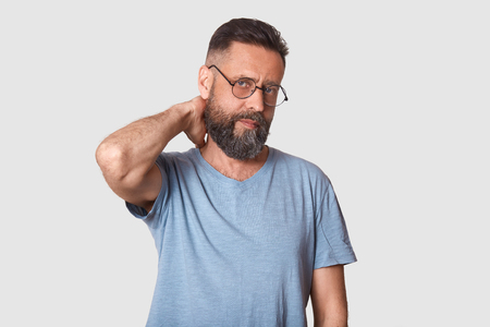 Photo pour Tired unemotional handsome executive looks firmly at camera, holding his arm behind, making neck massage after hard working day. Middle aged black haired model wearing stylish specs and t shirt. - image libre de droit