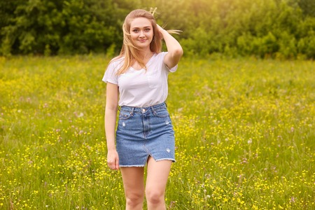Foto de Outdoor shot of pretty blond woman wearing white casual t shirt and denim skirt, posing in meadow, touching her fair hair, looking at camera with pleasant facial expression. Happiness concept. - Imagen libre de derechos