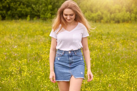 Foto de Outdoor shot of young beautiful Caucasian girl in white t shirt and blue denim skirt posing against sunset in meadow, looking down, attractive female looking down. Lifestyle and happiness concept. - Imagen libre de derechos