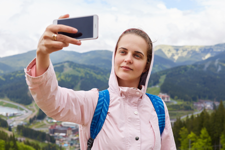 Photo for Shot of pretty young female tourist makes selfie in mountain, woman traveler being photographed outdoor against beautiful landscape. Traveling, lifestyle, adventure and active vacations concept. - Royalty Free Image