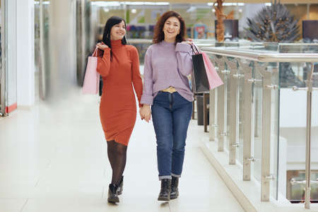 Photo pour Full length portrait of young females posing in mall with shopping bags, women wearing casual attires, holding hands, expressing happiness, buying new attires. - image libre de droit
