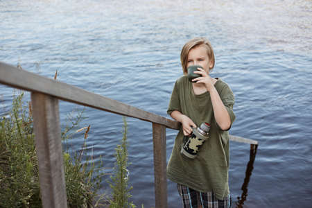 Photo pour Blond little boy drinking hot tea from over river, male child spending time in open air, wearing green t shirt, enjoying hot beverage while posing near water. - image libre de droit
