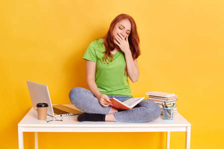 Photo for Adorable red haired tired sleepy woman sitting on her desk with books and computer, keeps eyes closed, covering her mouth while yawning, spending long hours studying against yellow wall. - Royalty Free Image