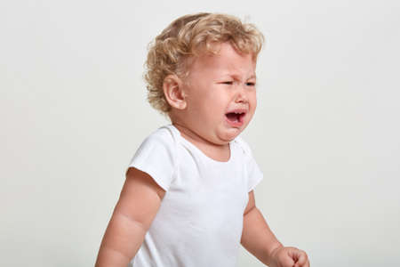 Photo for Little boy wearing t shirt cries, being in bad mood, looking away, posing isolated over white background, finding close person, having blond curly hair. - Royalty Free Image