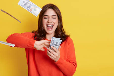 Photo for Portrait of very happy young Caucasian woman throwing out money banknotes, yelling something happily, having excited facial expression, keeps mouth opened, stands isolated over yellow background. - Royalty Free Image