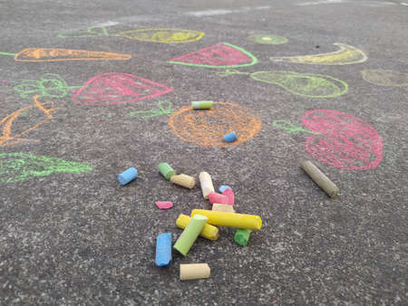 Foto de child's hand painting with colored chalk on the ground - Imagen libre de derechos