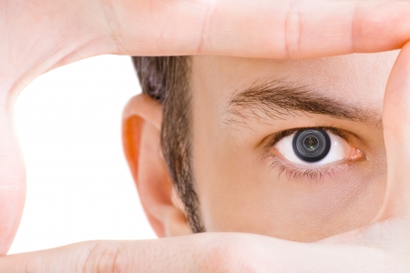 Man with objective instead eye looks through the frame
