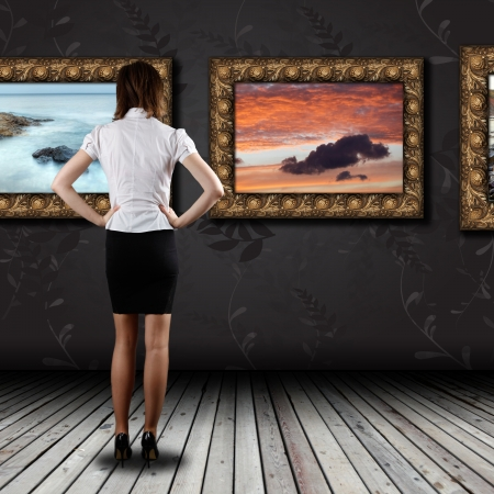 Photo pour Woman standing in the gallery and watching art - image libre de droit