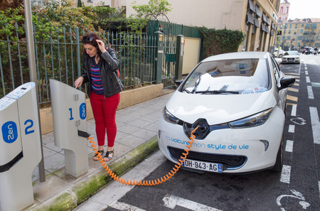 NICE, FRANCE APRIL 11, 2015: A woman is programming the Auto Bleue charging station to electrically charge a Renault Zoe electric car in Nice, France.