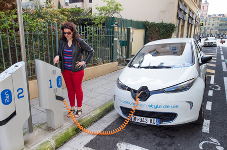 NICE, FRANCE – APRIL 11, 2015: A woman is programming the Auto Bleue charging station to electrically charge a Renault Zoe electric car in Nice, France.