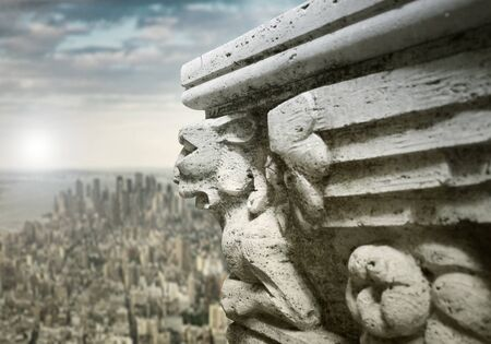 Beautiful sculpture on the ledge of a building with panoramic modern cityscape and sky  on the background