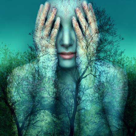 Photo for Surreal and artistic image of a girl who covers her eyes with her hands on a background of trees and sky - Royalty Free Image