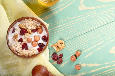 Wooden bowl with yogurt with rolled oats, nuts and dried cranberries, spoon and honey jar on yellow fabric on turquoise wooden table. Top view, flat lay, copy space.