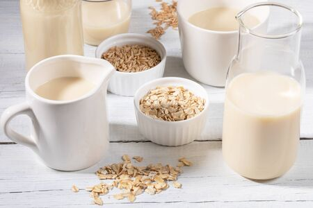 Photo pour Close-up glass bottle and mug with oat milk and bowls with oat seeds and flakes on white wooden table. - image libre de droit