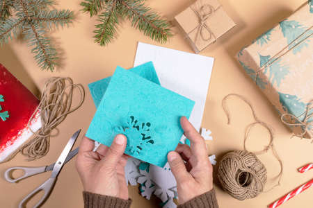 Photo pour DIY instruction. Step by step tutorial. Making Xmas toy snowflake of felt. Step 3 - Neatly take out details of snowflakes from substrates. Top view, flat lay. - image libre de droit