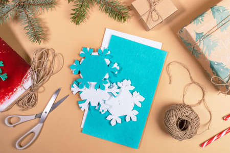 Photo pour DIY instruction. Step by step tutorial. Making Xmas toy snowflake of felt. Step 2 - Take out already finished parts snowflakes and substrates with applied half-cut snowflakes. Top view, flat lay. - image libre de droit
