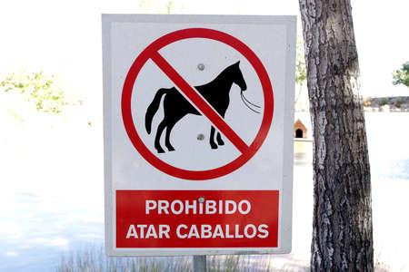 TERUEL, SPAIN - 06 October 2020: Vertical sign that says in Spanish forbidden to tie horses