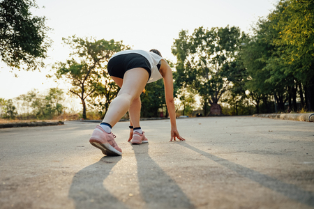 Foto per Woman runner in running start pose. Woman runner in running start pose on the road. Sport tight clothes. Bright sunset, blurry background - Immagine Royalty Free