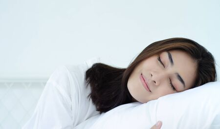 Photo for Beautiful woman sleeping in the bedroom. Woman lying face down on the bed.Girl wearing a pajama sleep on a bed in a white room in the morning.Warm tone. - Royalty Free Image