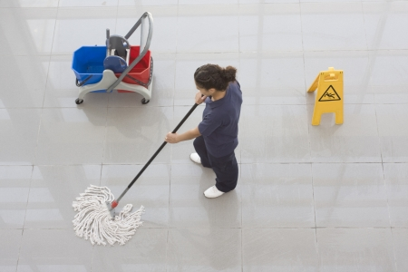 Photo pour A worker is cleaning the floor with equipment - image libre de droit